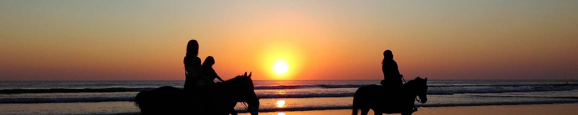 two people horse-riding along a beach at sun-set